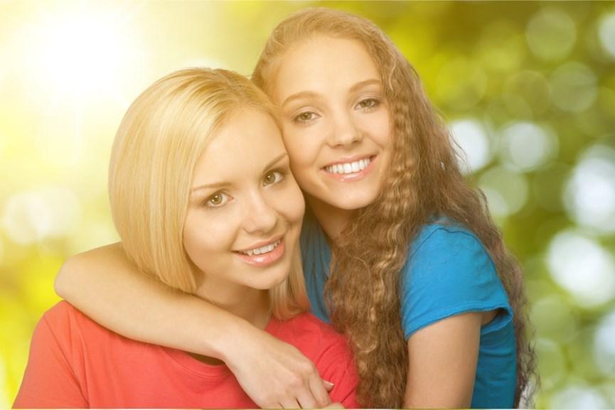 Μαμά και έφηβη κόρη αγκαλιάζονται και χαμογελούν